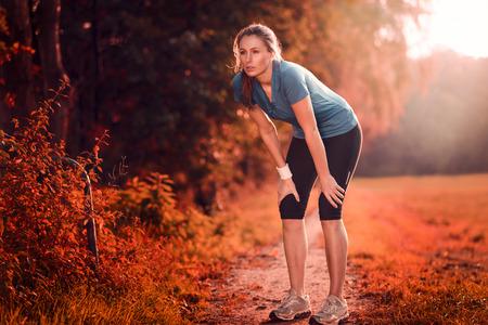 Jonge atletische vrouw die een pauze van training staande rust haar handen op haar knieën op een landelijke weg door de weelderige landbouwgrond in een gezondheids-en fitness concept