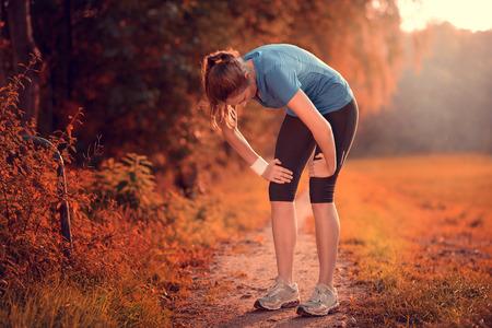 Mujer atlética joven que toma un descanso del entrenamiento de pie descansando sus manos sobre sus rodillas en una pista rural a través de exuberantes tierras de labranza en un concepto de salud y fitness Foto de archivo