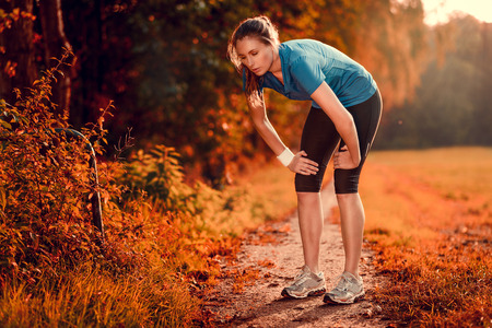 Young athletic woman taking a break from training standing resting her hands on her knees on a rural track through lush farmland in a health and fitness concept