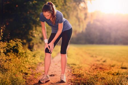 Jonge vrouw limbering up voor de training oefeningen om haar spieren op een land weg in de ochtend licht rekken