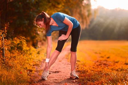 masaje deportivo: Mujer joven ejercicios de calentamiento antes del entrenamiento haciendo ejercicios para estirar sus músculos en un camino rural en la luz de la mañana Foto de archivo