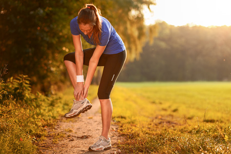 Young woman limbering up before training doing exercises to stretch her muscles on a country path in morning light