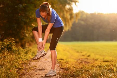 Junge Frau, die Lockerungsübungen vor dem Training Übungen, um ihre Muskeln auf einem Feldweg im Morgenlicht zu strecken
