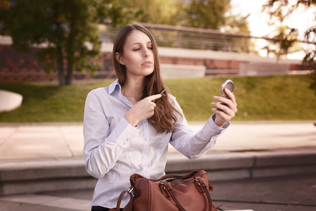 combing hair: Young woman refreshing her hairstyle in an urban street watching herself in a small handheld mirror as she combs her long brown hair Stock Photo