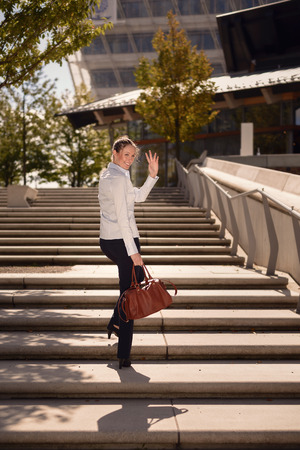 emphasizing: Young Woman in Business Attire with Elegant Bag Walking on Concrete Stairs Going Up While Take a Pose for a While and Wave One Hand, Emphasizing Goodbye. Stock Photo
