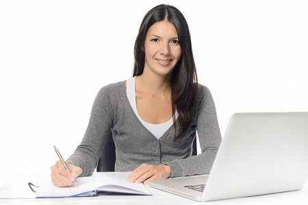Smiling attractive young woman working at a desk with her laptop computer writing notes in a notebook conceptual of a hardworking office worker or businesswoman, or a student studying by e-learning