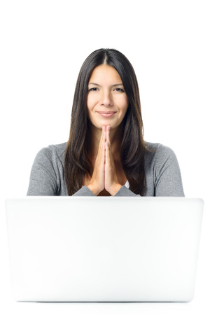 relieved: Young student or business woman with a beaming smile and hands clasped in gratitude or prayer sitting at her desk behind a laptop computer after solving a worrying problem Stock Photo