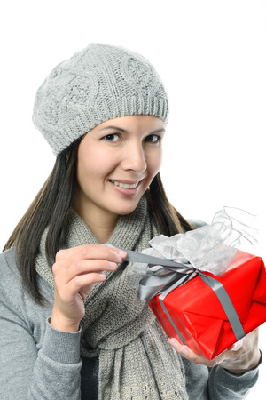Close up Pretty Smiling Young Woman in Winter Fashion Holding Gift Box While Looking at Camera, Isolated on White Background. photo