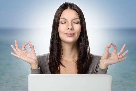 , 캡처 오션 배경을 폐쇄하는 요가 제스처와 눈에 두 손으로 생각 노트북 컴퓨터를 사용하여 꽤 젊은 여자를 닫습니다.