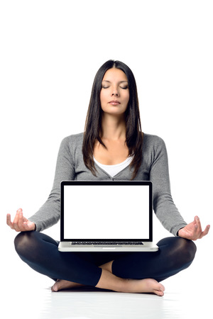 long hair woman: Pretty Long Hair Woman in Meditating Pose with Closed Eyes and Crossed Legs While Facing a Laptop in Front. Isolated on White Background. Stock Photo