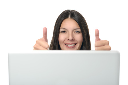 Attractive Woman Showing Thumbs up Sign on Both Hands In Front of Computer Device. Isolated on White Background. photo