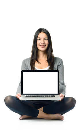 Smiling woman displaying her blank laptop screen to the camera as she sits bare foot and cross-legged on the ground with her computer balanced on her lap over a white background photo