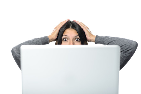 Middle Aged Woman in Surprise Facial Expression with Both Hands on the Head Facing a Computer. Isolated on White Background. Standard-Bild