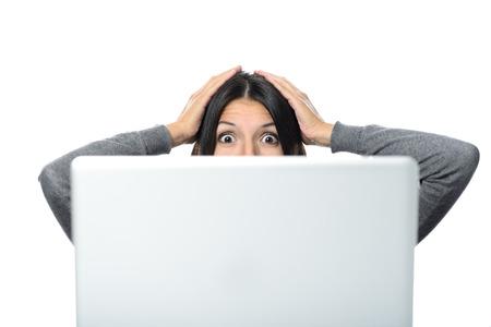 gestos de la cara: Mujer de mediana edad en la sorpresa Expresión facial con ambas manos en la cabeza mirando hacia un ordenador. Aislado en el fondo blanco.