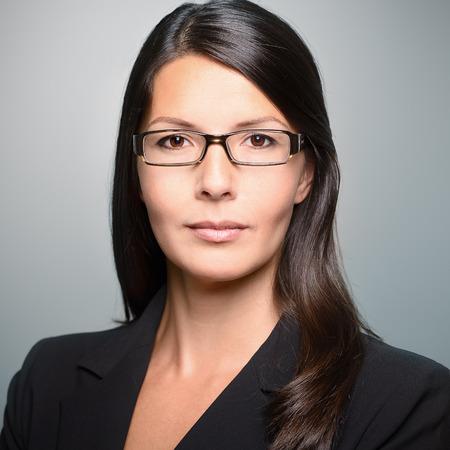 カメラ、コピー スペースと灰色の背景に彼女の顔のクローズ アップを直接見て気配りのある式を持つ魅力的なスタイリッシュな若い実業家 写真素材
