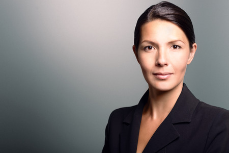 Attractive stylish businesswoman with an attentive expression looking directly at the camera, closeup of her face on a grey background with copy space