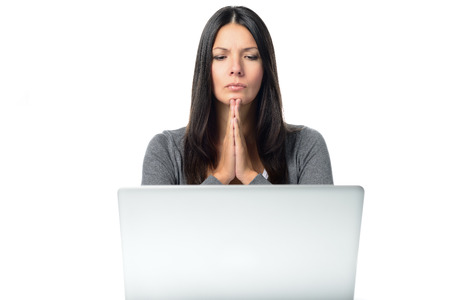relieved: Young student or business woman with a stern expression and hands clasped in hope or prayer sitting at her desk behind a laptop computer