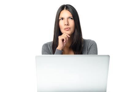 그녀의 손으로 그녀의 턱과 진지한 표정으로 공중에 응시하는 그녀의 책상에서 그녀의 노트북 뒤에 앉아있는 걱정스러운 찡그린 앉아있는 매력적인
