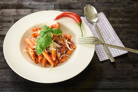 Plate of penne pasta with arrabiata sauce, a hot spicy sauce with garlic, tomato, chili pepper and olive oil, garnished with fresh basil and parmesan cheese, overhead view photo