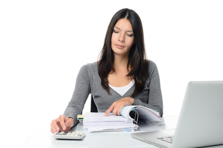Young woman checking a report or invoices in a large office binder doing manual calculations to verify the figures on a desktop calculator photo