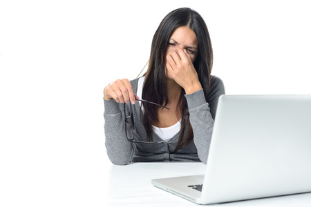 Young woman suffering from eye strain at her laptop removing her eyeglasses to rub her eyes with her finger with a pained expression, on white