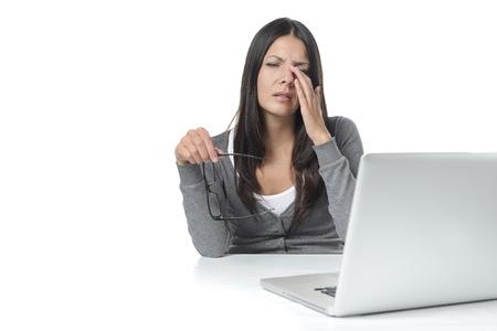 cansancio: Mujer joven que sufre de la tensión del ojo en su computadora portátil que quita sus gafas para frotarse los ojos con el dedo con una expresión de dolor, en blanco Foto de archivo