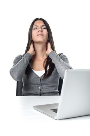 Aantrekkelijke jonge vrouw zit op haar laptop wrijven haar nek met een grimas om de stijfheid te verlichten na de vergadering op de computer te lang