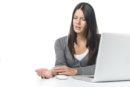 overworking: Young businesswoman rubbing and massaging her wrist to relieve cramps after using a computer mouse for too long at a stretch, on white
