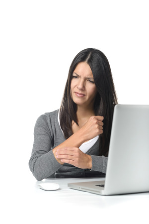 omitted: Young businesswoman rubbing and massaging her forearm to relieve cramps after using a computer mouse for too long at a stretch, on white Stock Photo