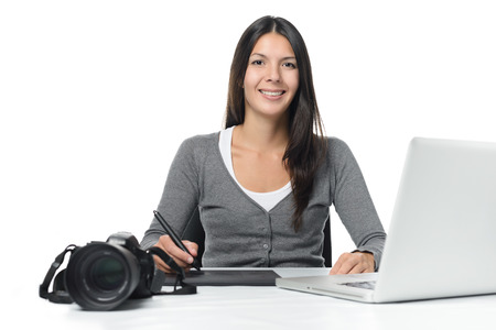 downloaded: Female photographer smiling as she does her edits of her recently downloaded files on a laptop using a tablet and stylus with her camera alongside on the desk, over white Stock Photo