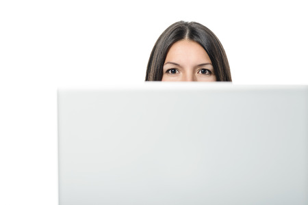 looking behind: Young woman looking at camera with intelligent eyes while hiding behind the monitor of a desk computer, with copy space on white