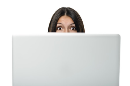 Businesswoman looking over the top of her computer screen at the camera with a look of surprise, shock, amazement and admiration with her mouth open and eyes wide