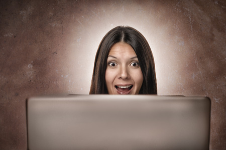 Attractive young businesswoman looking in amazement and delighted surprise at the camera from behind her computer monitor isolated on white photo