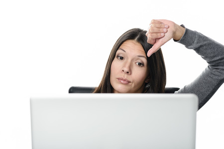 malcontent: Unsatisfied Young Woman Working with Laptop Showing Thumbs Down Sign. Isolated on White Background.