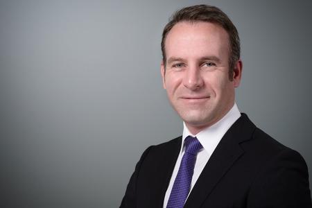 Knappe modieuze zakenman met een aandachtige uitdrukking die direct de camera, op een grijze achtergrond met exemplaarruimte bekijkt