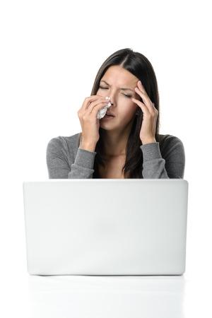 hemorragias: Mujer joven con fiebre y escalofríos por la influenza de temporada que tengan un pañuelo a la nariz streaming y una mano a la frente mientras ella hace una mueca de dolor de un dolor de cabeza