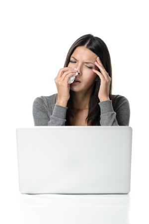 holding nose: Young woman with a fever and chills from seasonal influenza holding a tissue to her streaming nose and a hand to her forehead as she winces in pain from a headache