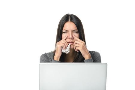 Jonge onderneemster met een ernstige sinusitis vergadering op haar bureau achter een laptop computer grimassen van de pijn en houdt haar vingers aan haar sinussen, op wit