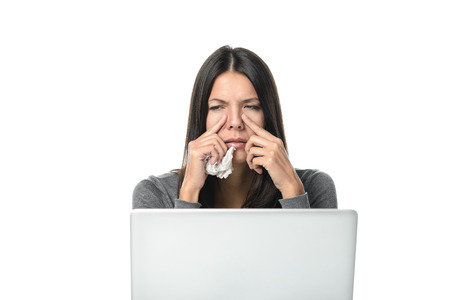 sinusitis: Young businesswoman with severe sinusitis sitting at her desk behind a laptop computer grimacing in pain and holding her fingers to her sinuses, on white