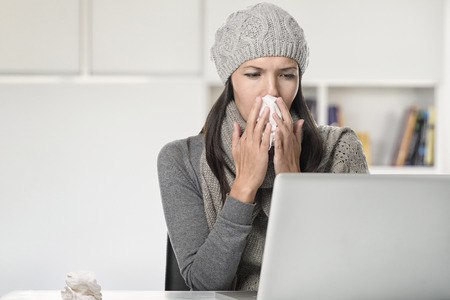 sinusitis: Young businesswoman with a seasonal cold and flu sitting behind her computer blowing her nose on a tissue, sitting in her office Stock Photo