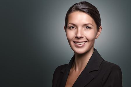 Attraktive stilvolle Geschäftsfrau mit einem aufmerksamen Ausdruck Blick direkt in die Kamera, Nahaufnahme von ihr Gesicht auf einem grauen Hintergrund mit Kopie Raum