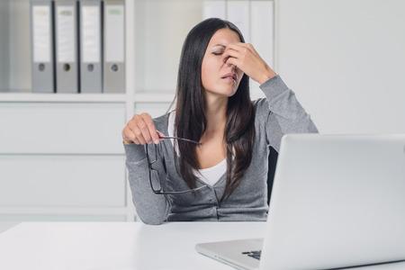 若い女性は苦しそうな表情で彼女の指で彼女の目をこするに彼女の眼鏡を削除する彼女のラップトップで眼精疲労に苦しんで