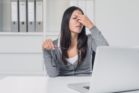 cansancio: Mujer joven que sufre de la tensión del ojo en su computadora portátil que quita sus gafas para frotarse los ojos con el dedo con una expresión de dolor