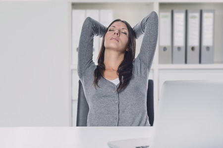 tilted: Young businesswoman enjoying a relaxing moment sitting in her chair at her desk with her hands clasped behind her head and eyes closed with a serene expression