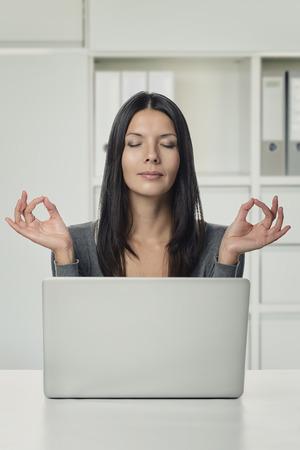 ojos cerrados: Cierre de la mujer bastante joven usando el ordenador portátil Pensar con las dos manos en gestos de yoga y los ojos cerrados, en la oficina
