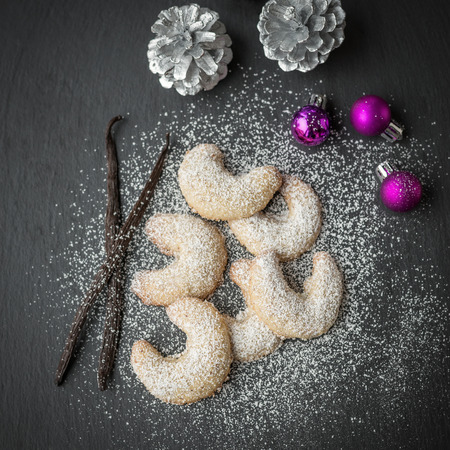 Freshly baked festive golden crescent cookies for Christmas and Advent sprinkled with icing sugar on a grey kitchen counter with christmas decorations, from above photo