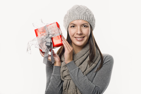 bonnet up: Close up Pretty Young Woman with red bonnet Holding Red Present Box with Gray Ribbons. Looking at Camera, isolated on White Background. Stock Photo