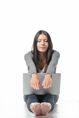 woman sitting on floor: Attractive young woman sitting barefoot on the floor with her laptop computer stretching her hands and feet relaxing while meditating with closed eyes and a look of serenity in a wellness concept Stock Photo