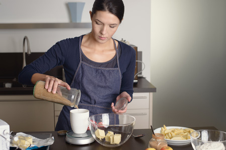 kitchen scale: Young housewife standing at the counter in her apron baking in the kitchen pouring fresh ingredients into a kitchen scale weighing them to add to her mixing bowl and butter