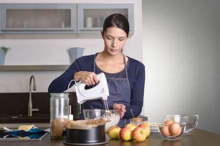 젊은 여자 그릇에 사과, 계란, 베이킹 깡통을 섞어 유리에 신선한 재료를 털기 위해 휴대용 믹서를 사용하여 그녀의 앞치마에서 카운터에 서서 부엌에 스톡 콘텐츠